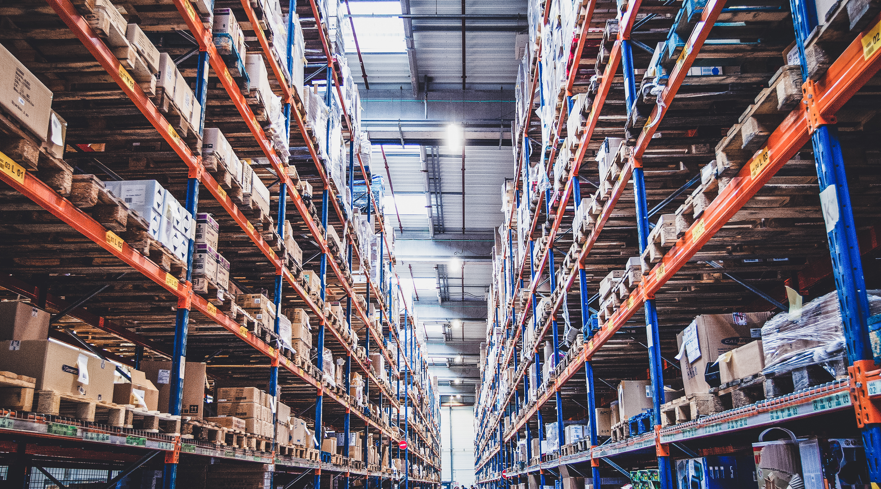 Photo of the inside of a warehouse. The shot is taken standing at the end of an aisle and you can view the entire length of the aisle. On either side is floor to ceiling racks of unidentifiable goods