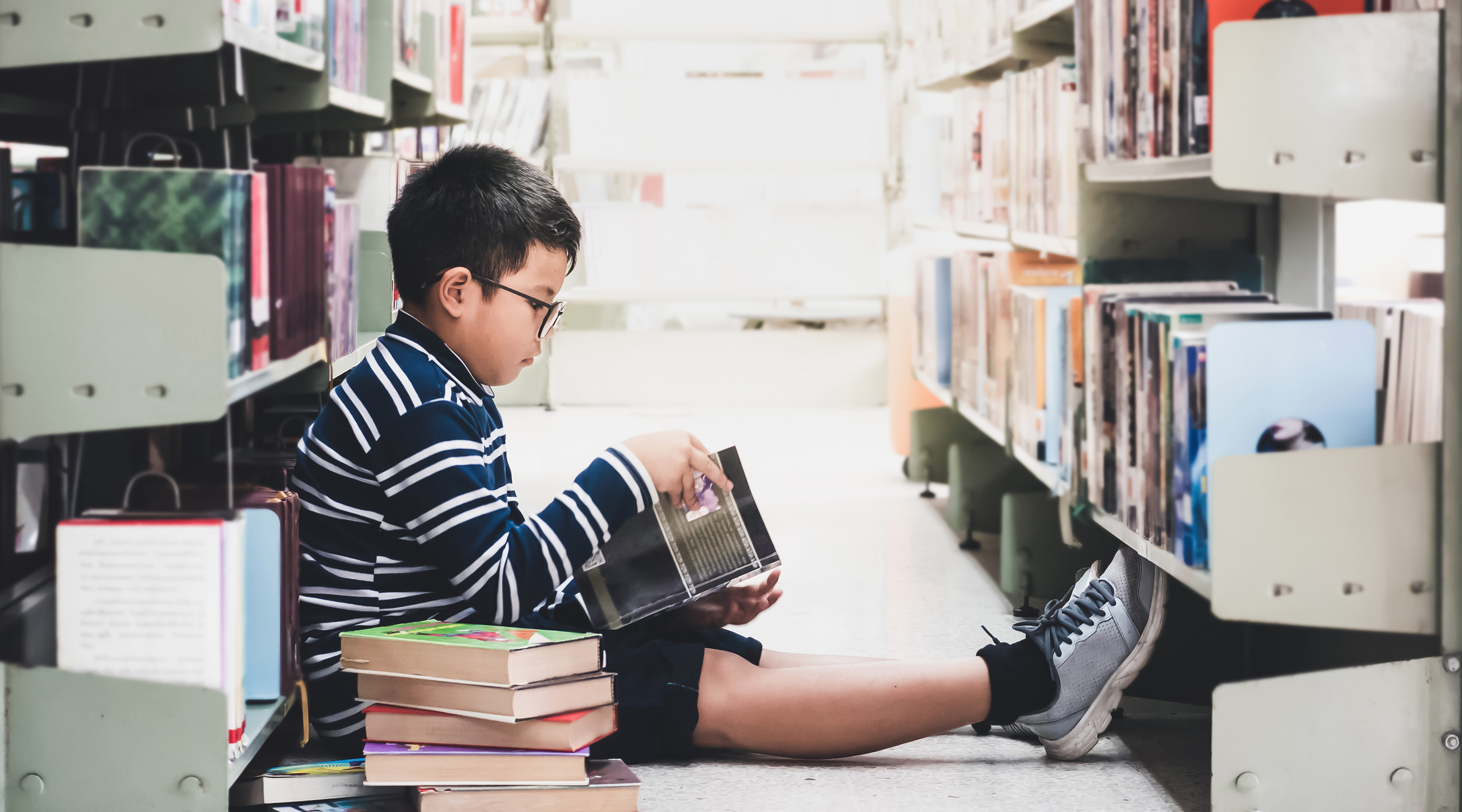 Image of a young male student sitting on the floor inside a school library reading a book as he leans against a wall of books