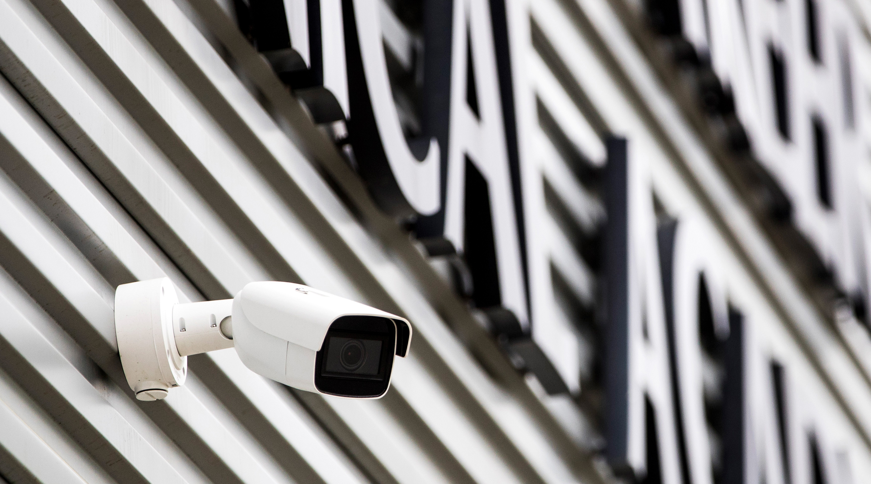 Close up Image of the side of a building focusing on a security camera