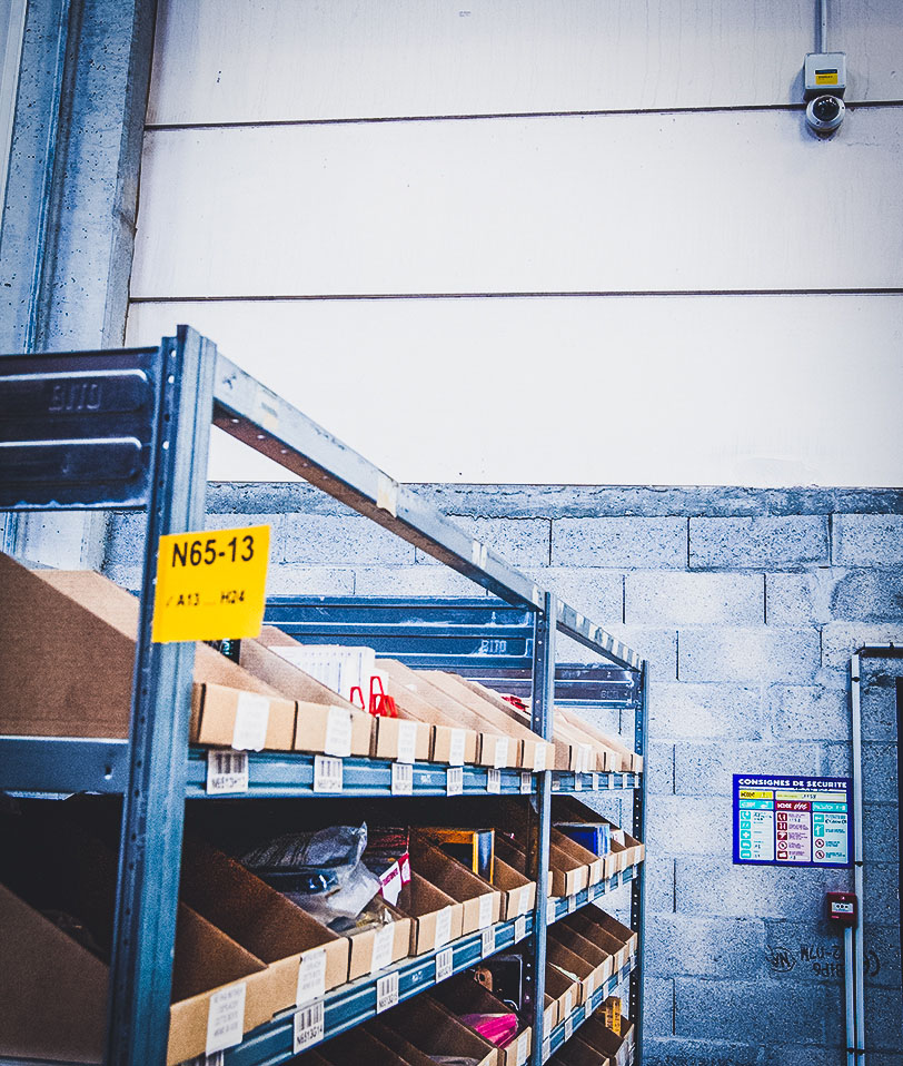 Close up shot of shelves in a warehouse next to an exit. On the wall is a STANLEY Security dome camera