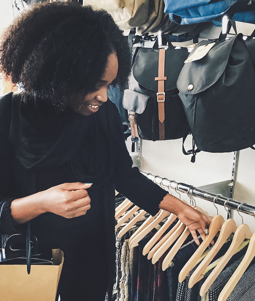 Closeup photo of a female customer browsing a rack of clothes in a store