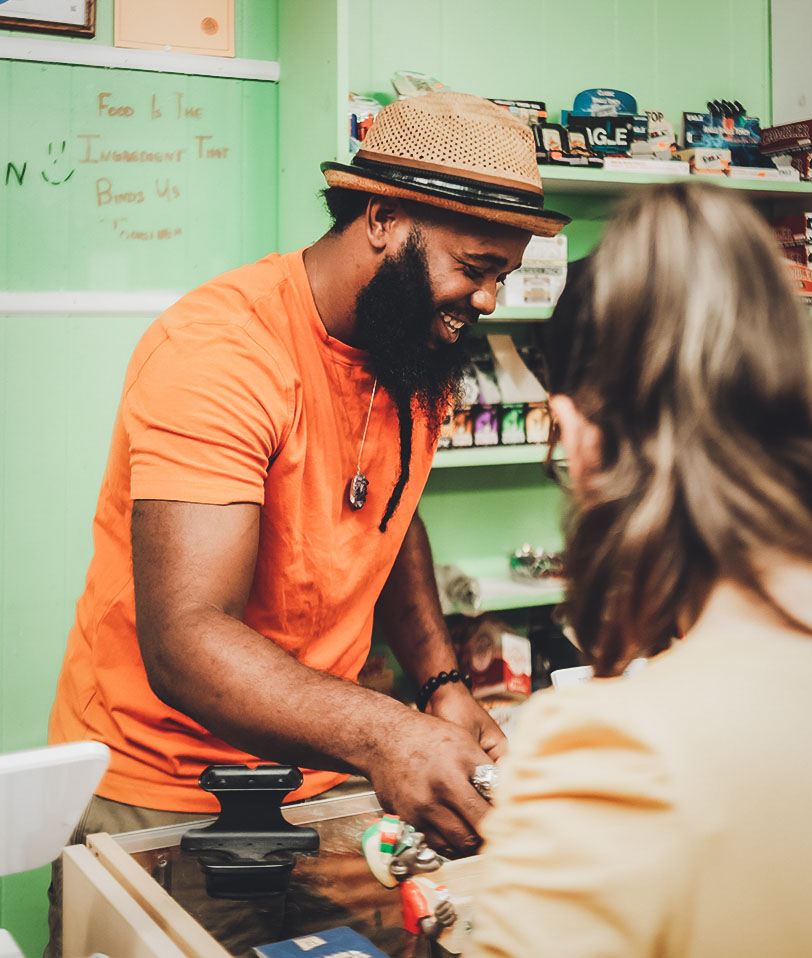 Image of a male shop employee in a hat checking out a female who is buying goods. THe man is smiling and preparing to pack the customers goods