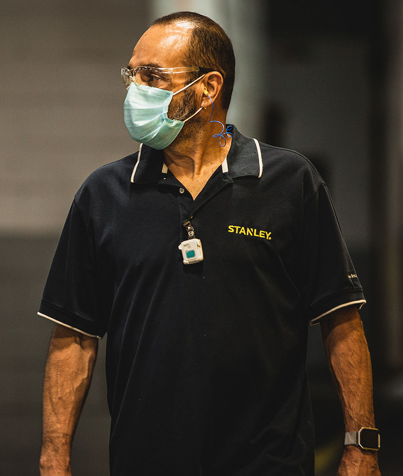 Photo of a male factory worker in PPE glasses and mask wearing a STANLEY Healthcare tracking badge. The man is walking towards the camera but looking to our left, his right