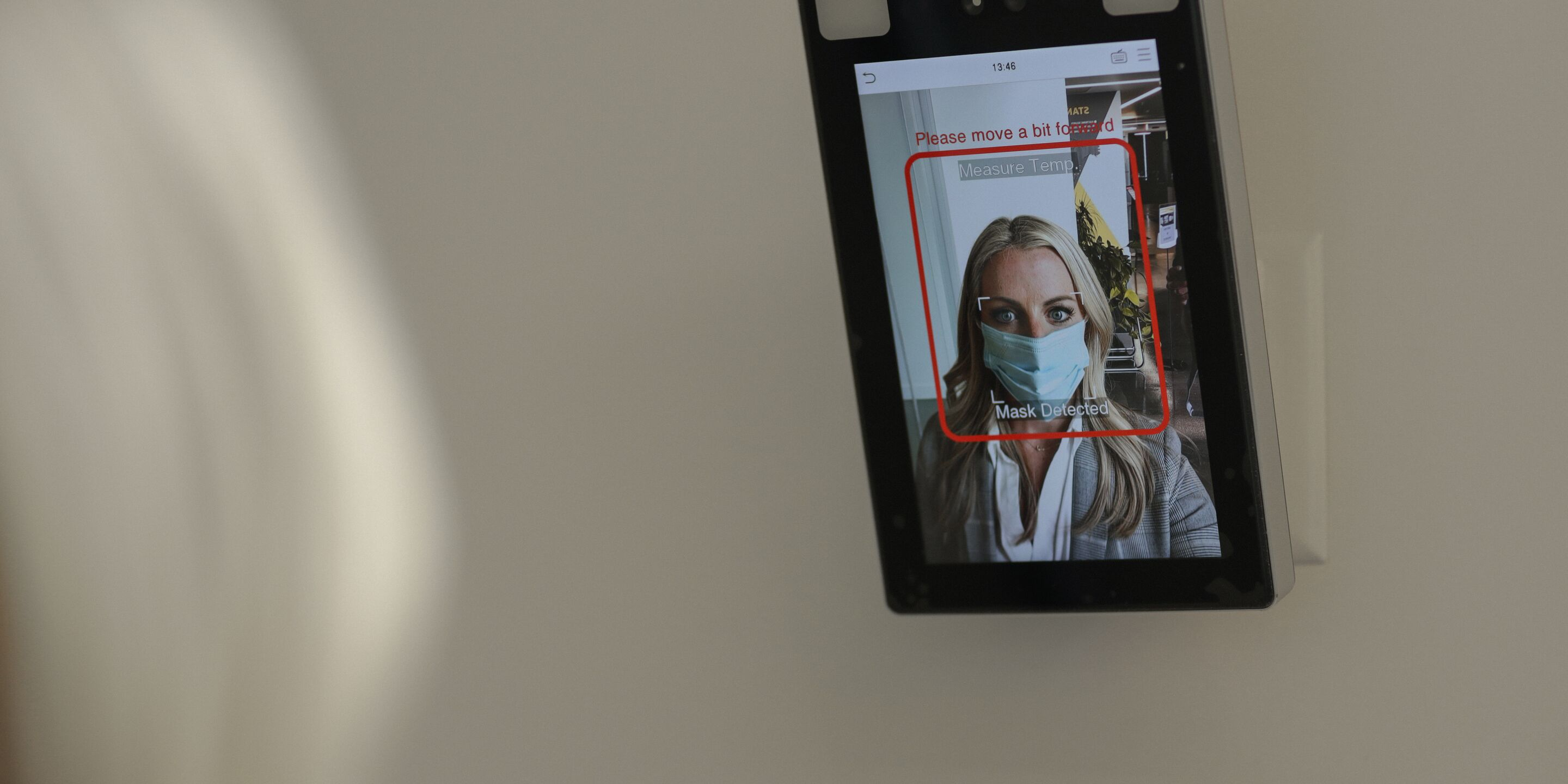 A blonde hair woman wearing a medical mask shown on a display screen that has detected she is wearing a mask