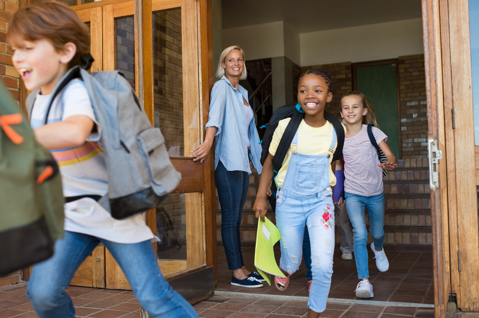 Image of school children outside the front entrance of a school walking towards to the entrance