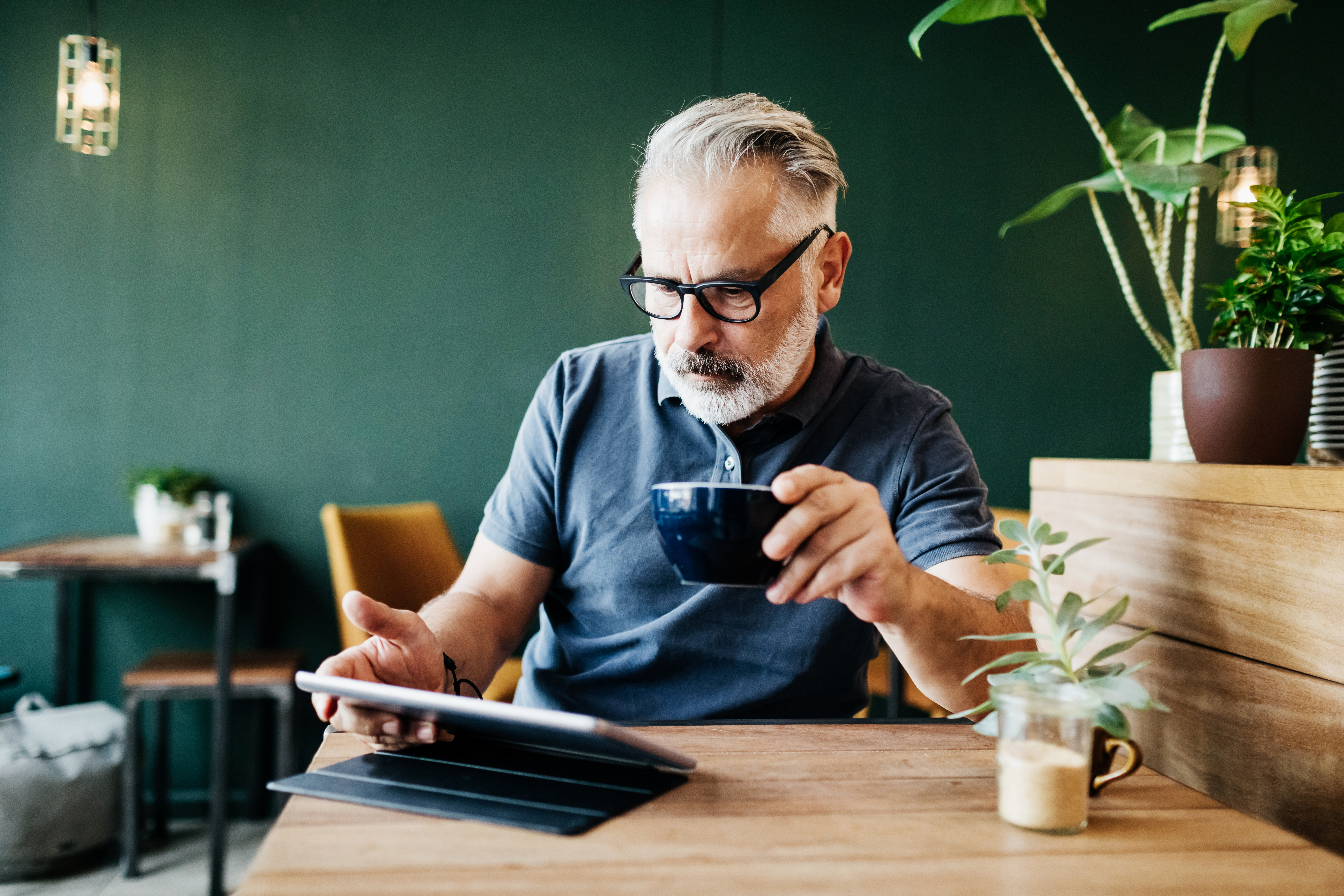 man reading on ipad with coffee connected