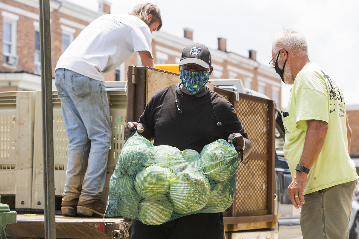 UWCM Volunteers unload donated cabbage and other produce for food handout event
