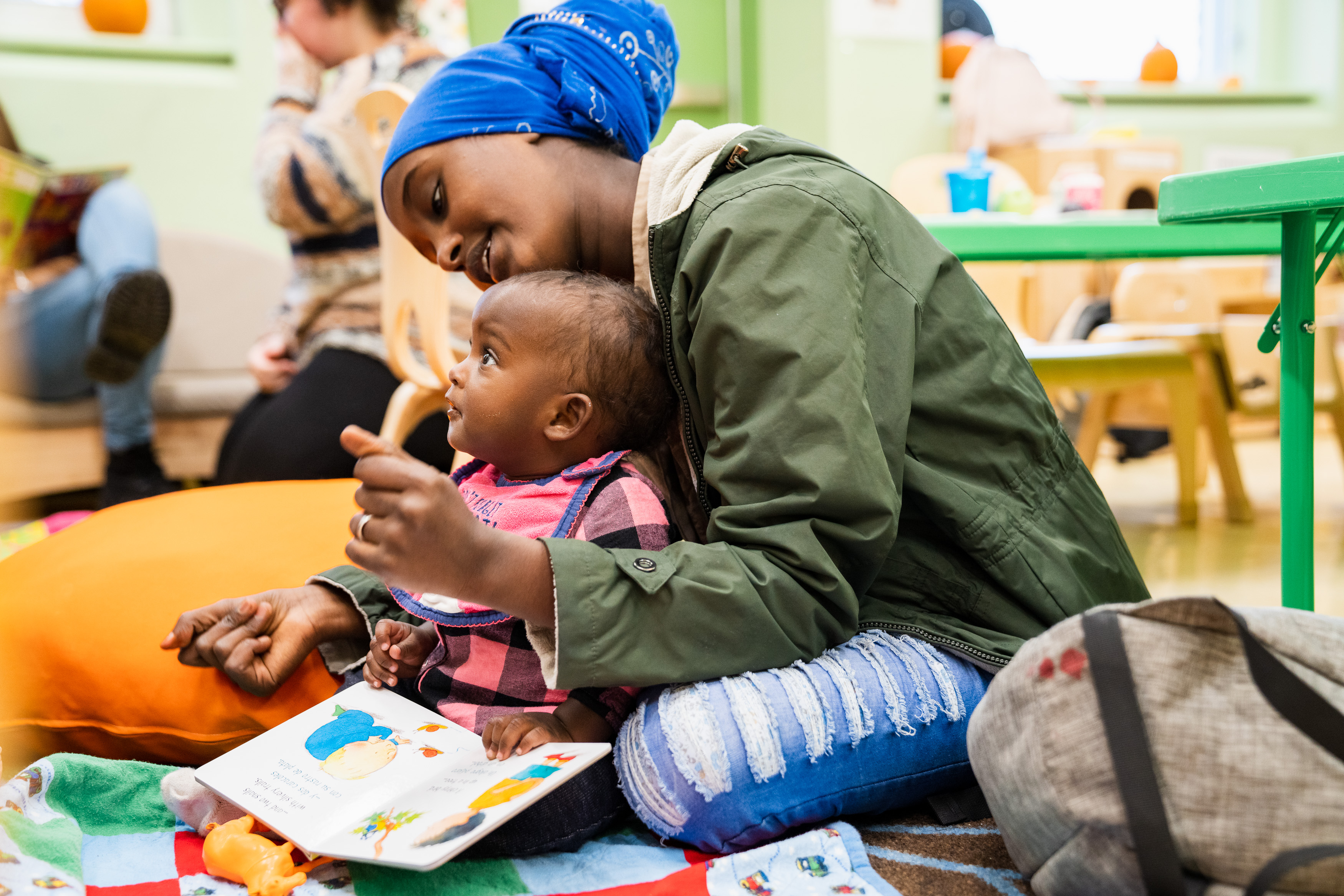 Photo of the UWCM Columbia Childcare facility: scene of a mother and child with a book on the floor reading together