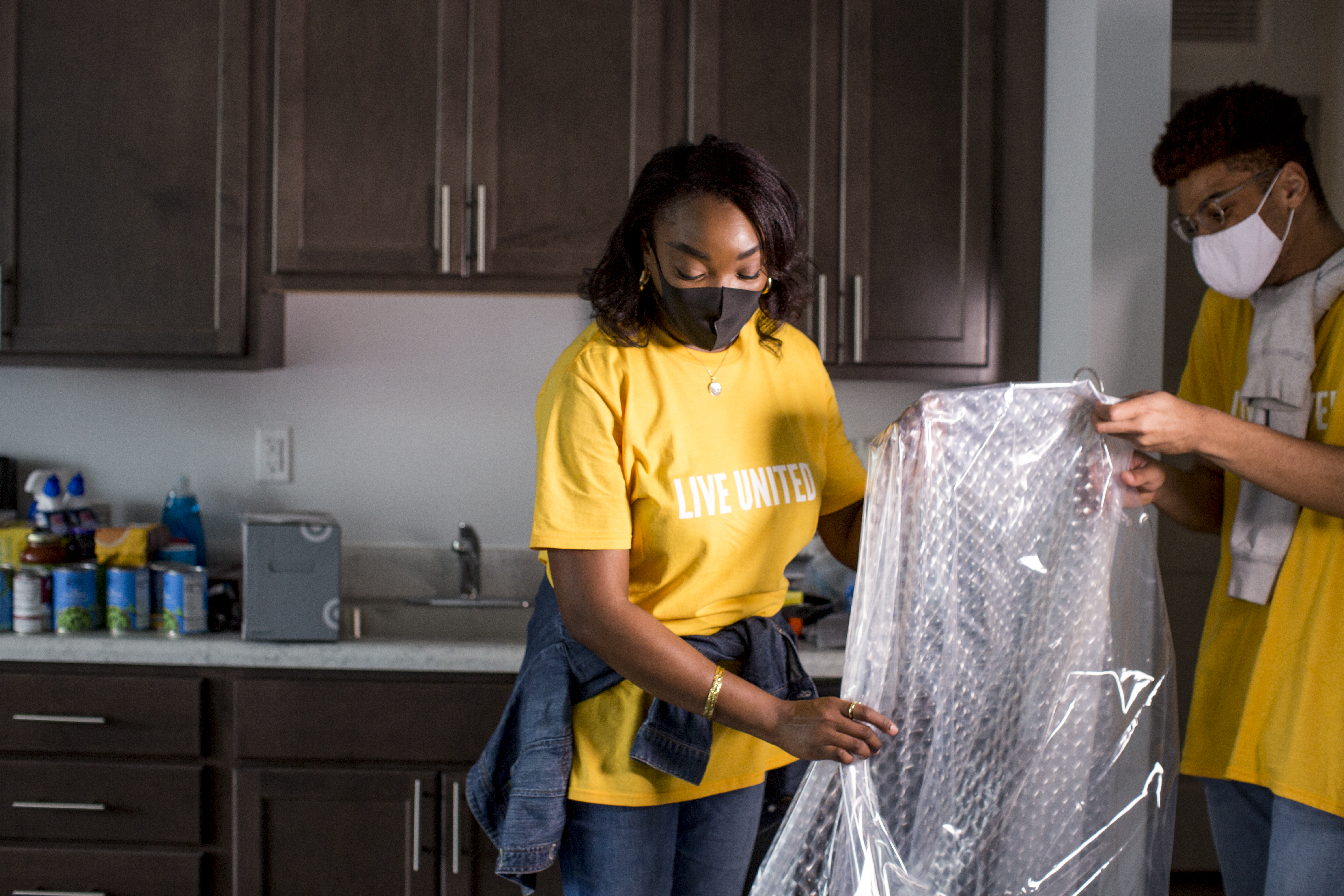 Photo of two volunteers wearing Live United shirts while unpacking household items in a new home for one of The Way Home project's recipients.
