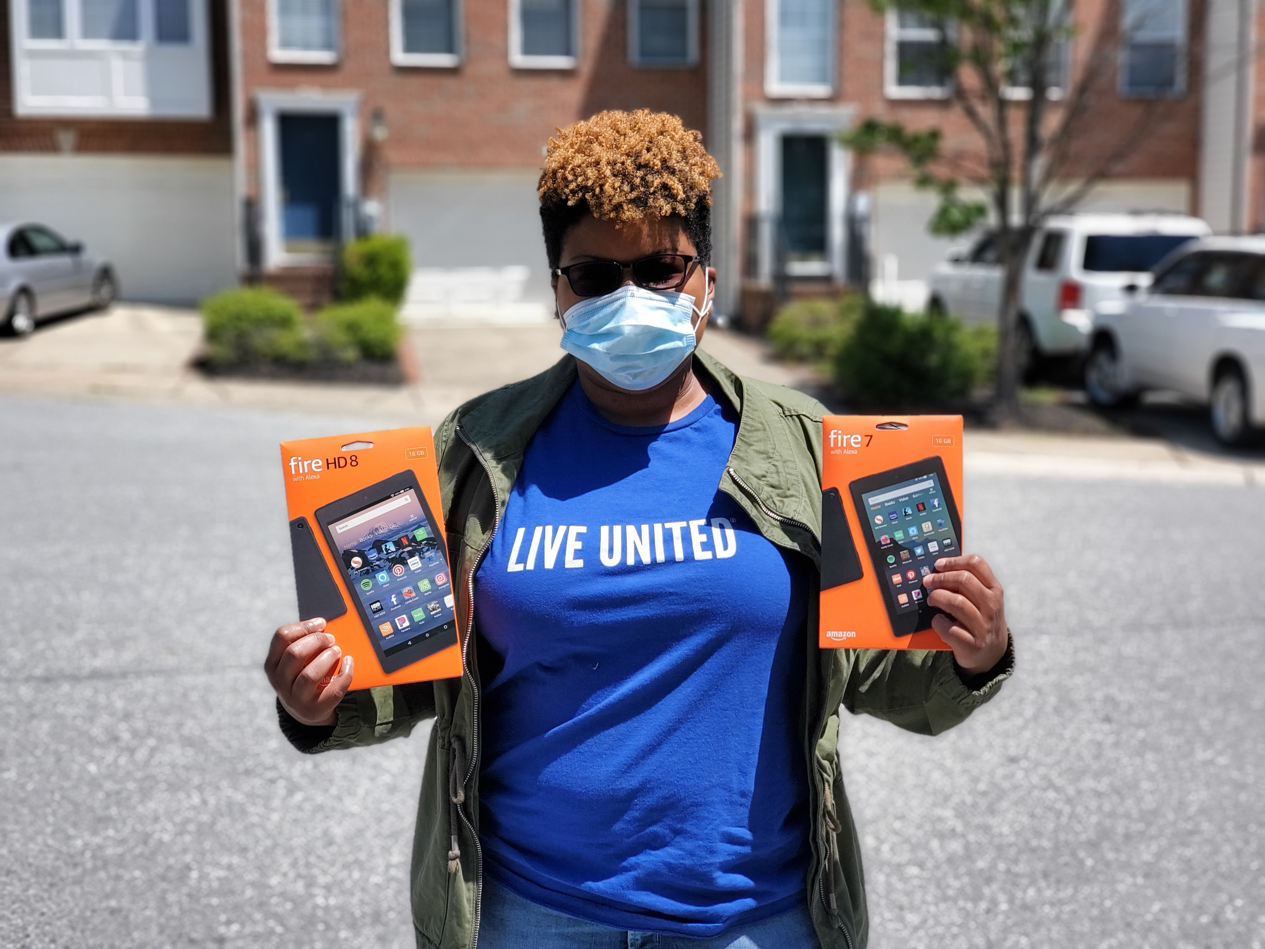 Tablet Distribution Photo: UWCM staff member in blue Live United shirt holding two donated tablets for distribution during delivery event