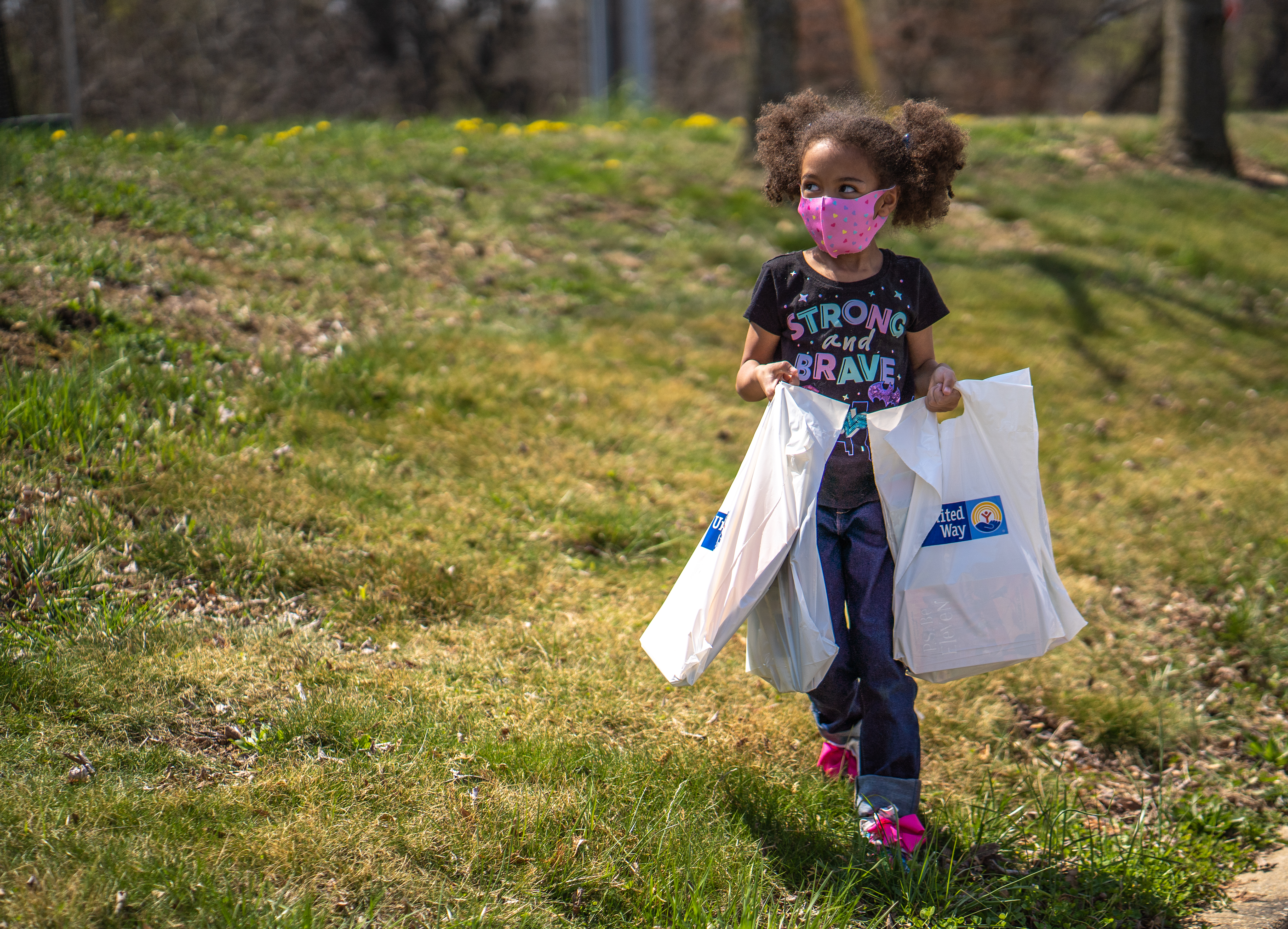 Cover Photo: Young girl holding United Way bags filled with donated books from Mobile Book Drive