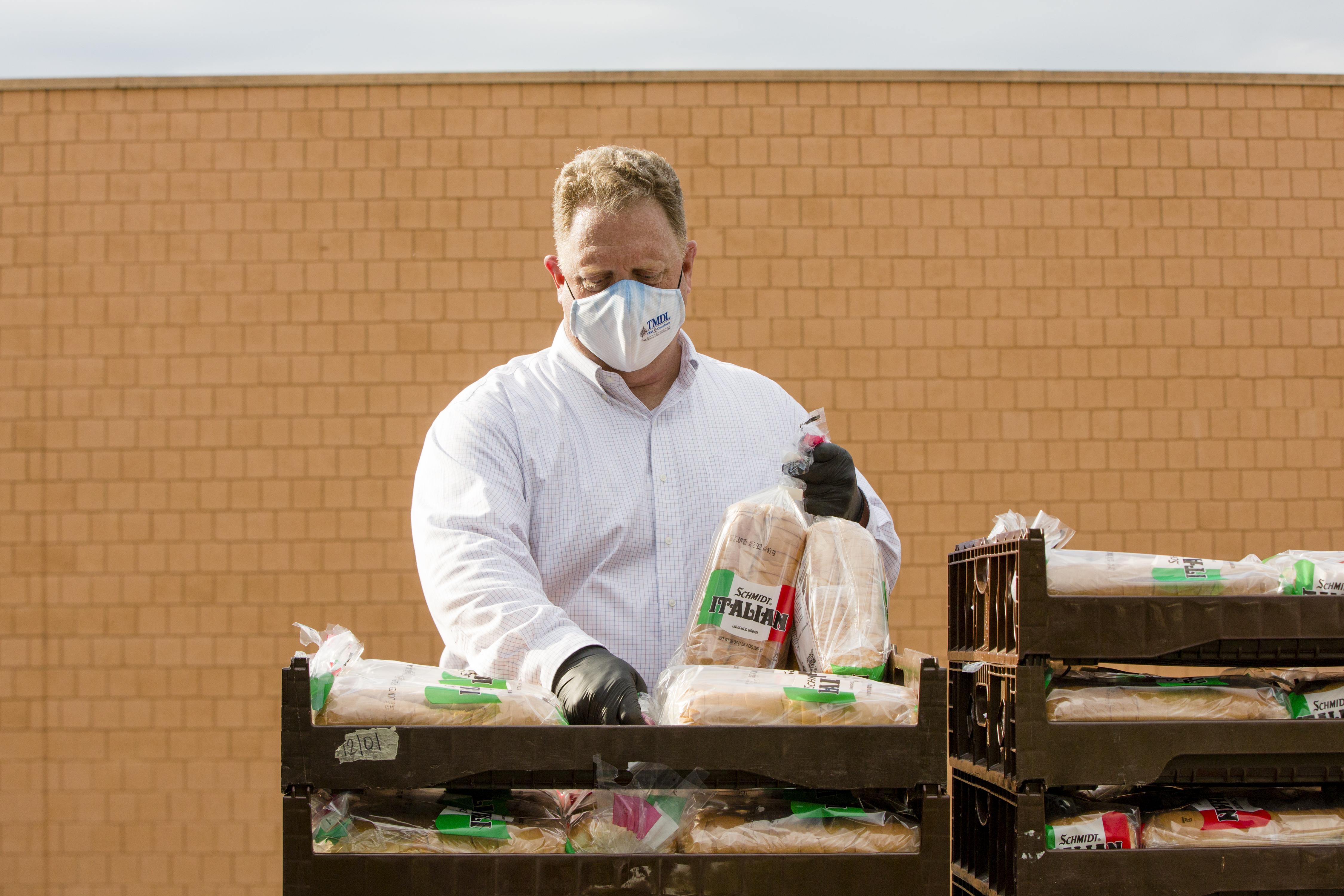 UWCM volunteer prepares stacks of bread during food handout event