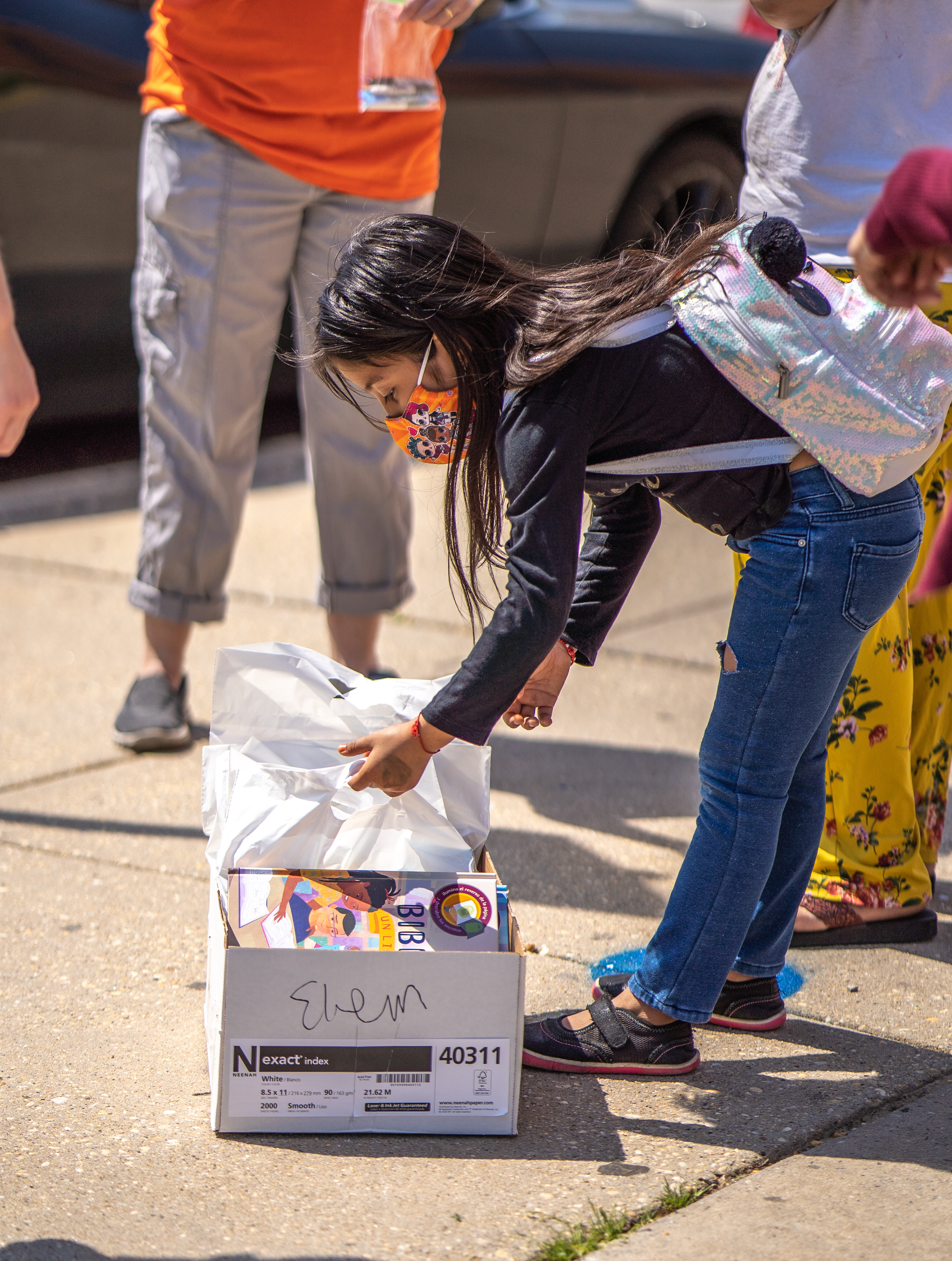 UWCM Mobile Book distribution photo - young girl sifting through a box of bagged books