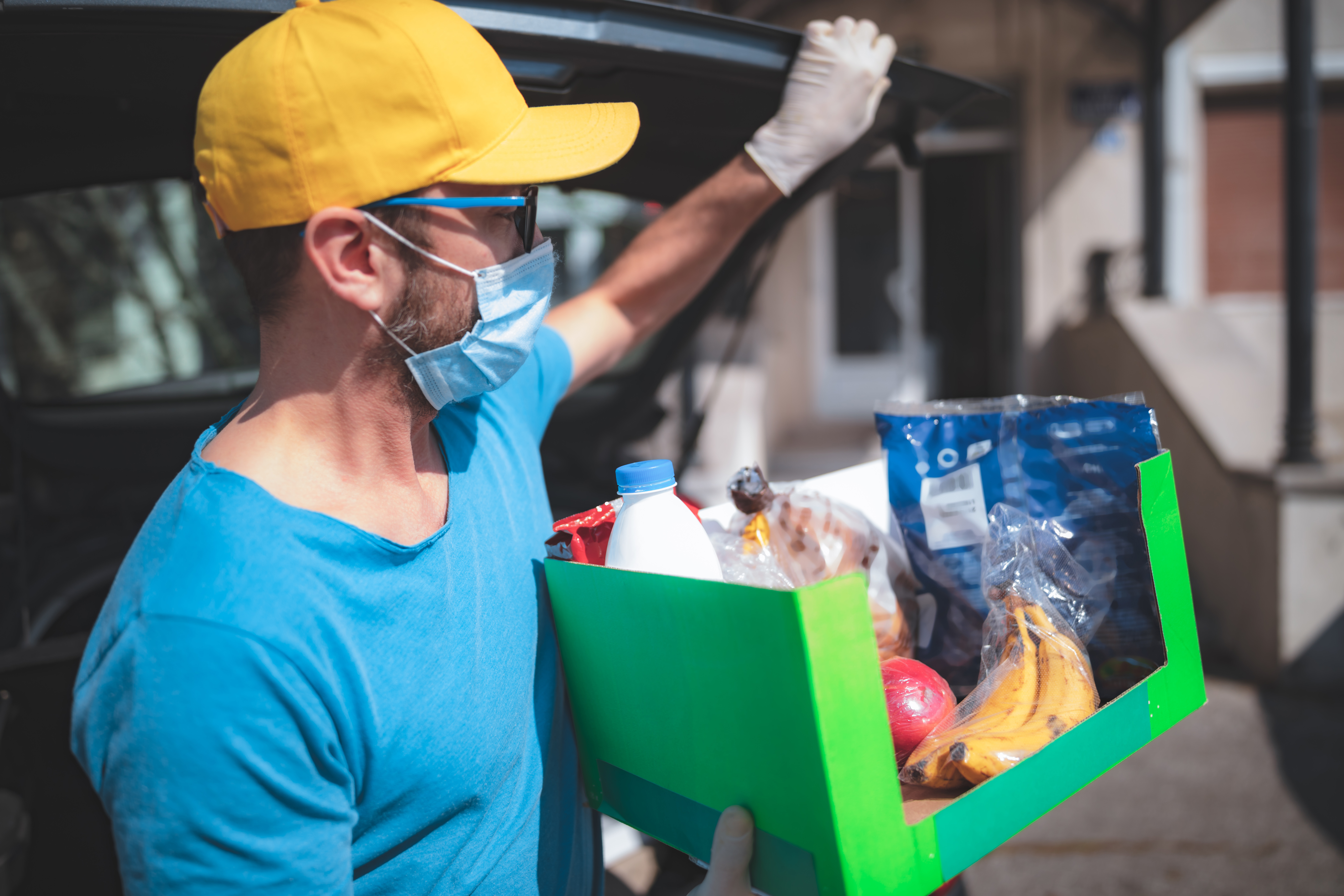 UWCM food distribution photo showing man with mask delivery package of groceries