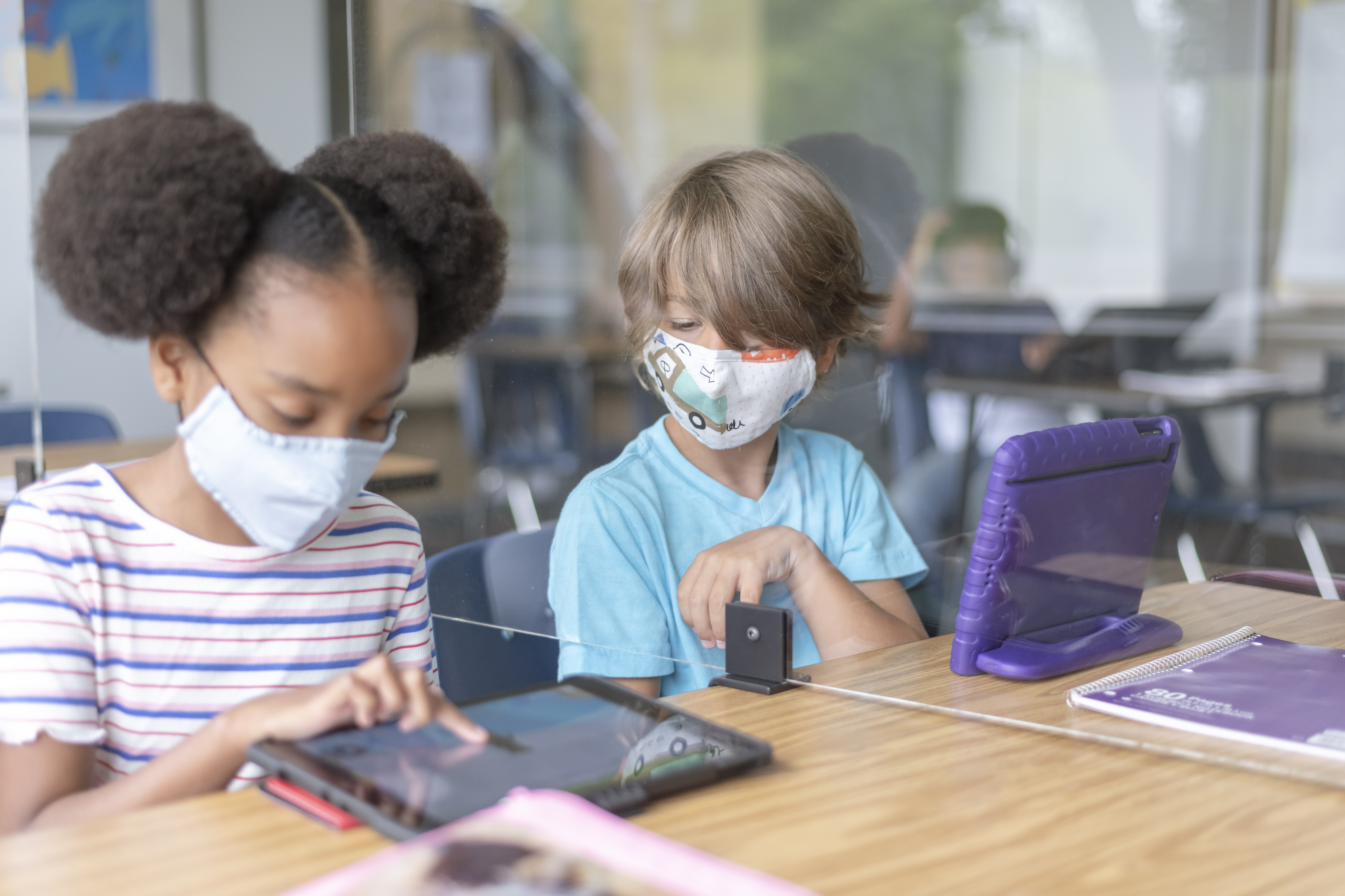 two children in classrooms, wearing masks, while on tablets