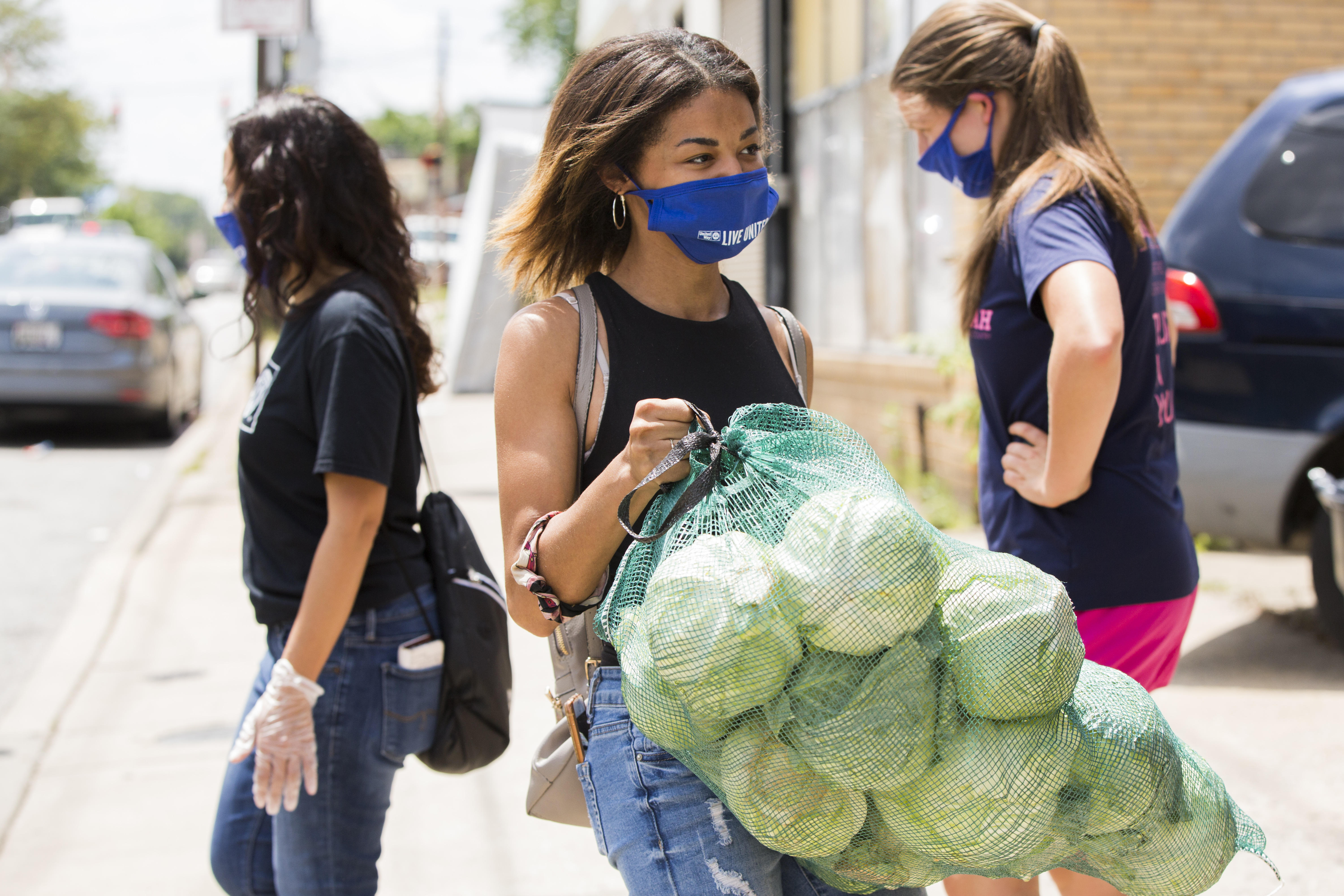 Women in blue Live United mask carrying a sack of cabbage for food distribution event