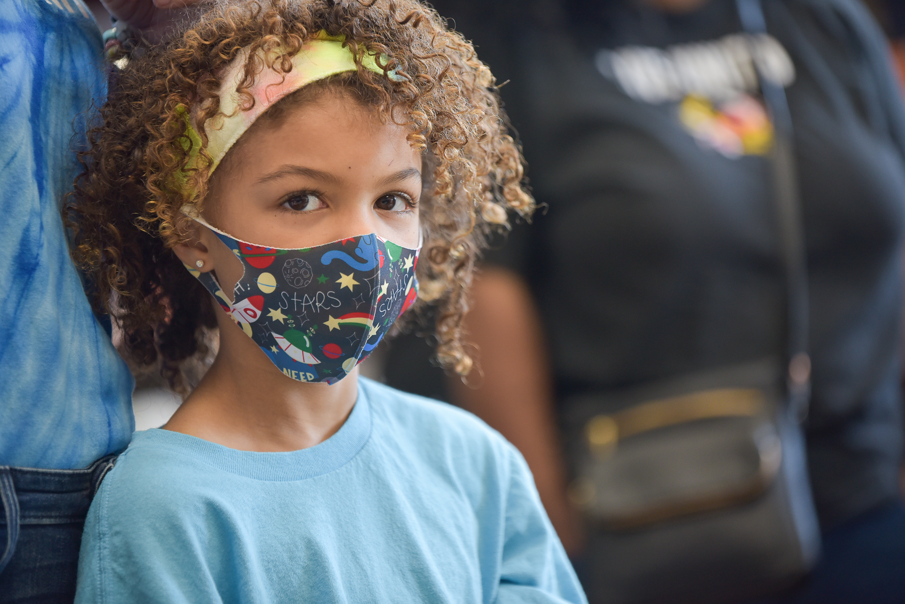 UWCM young volunteer in a mask