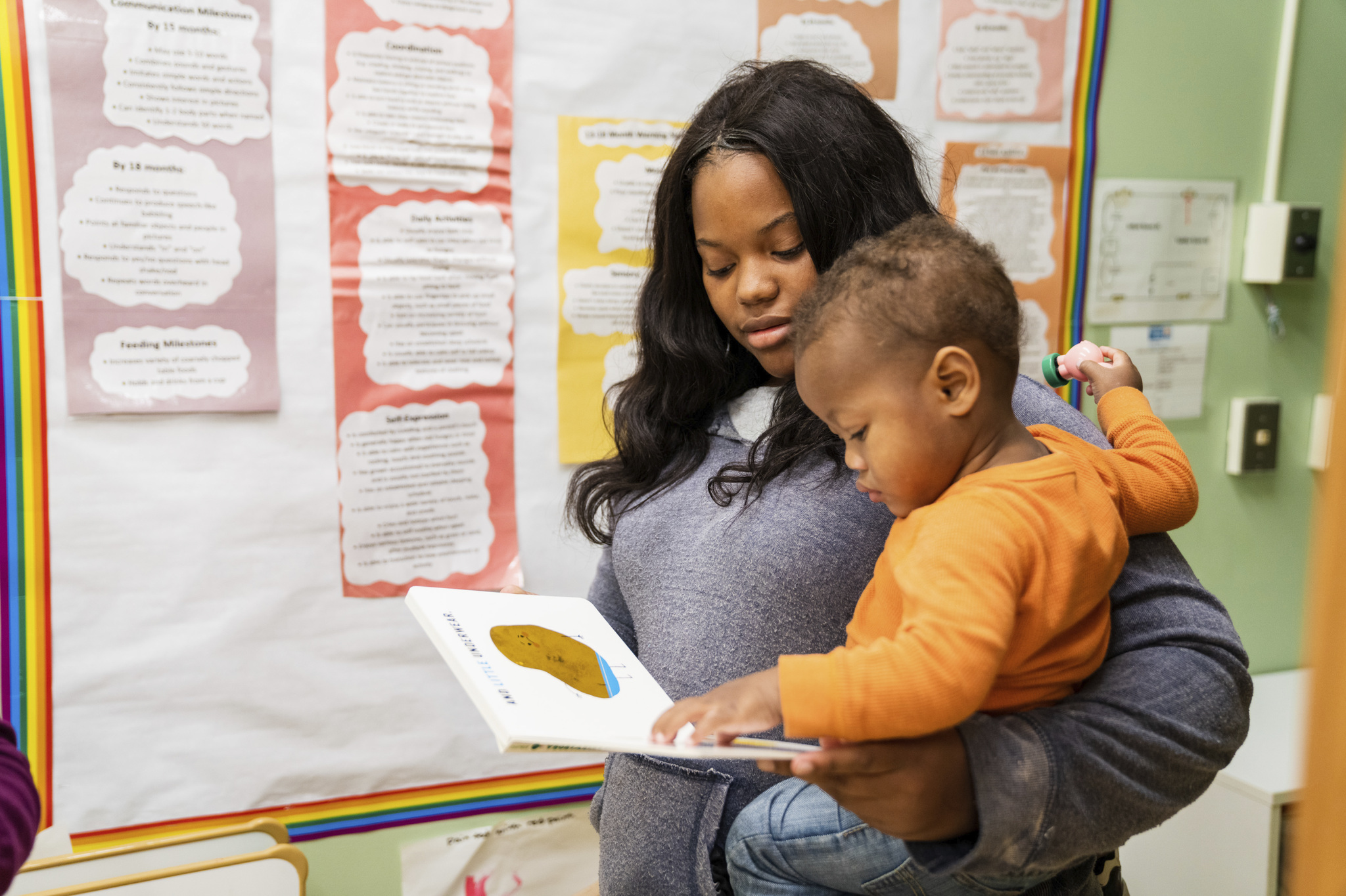 UWCM Columbia Childcare Photo of a mother with her toddler reading a book