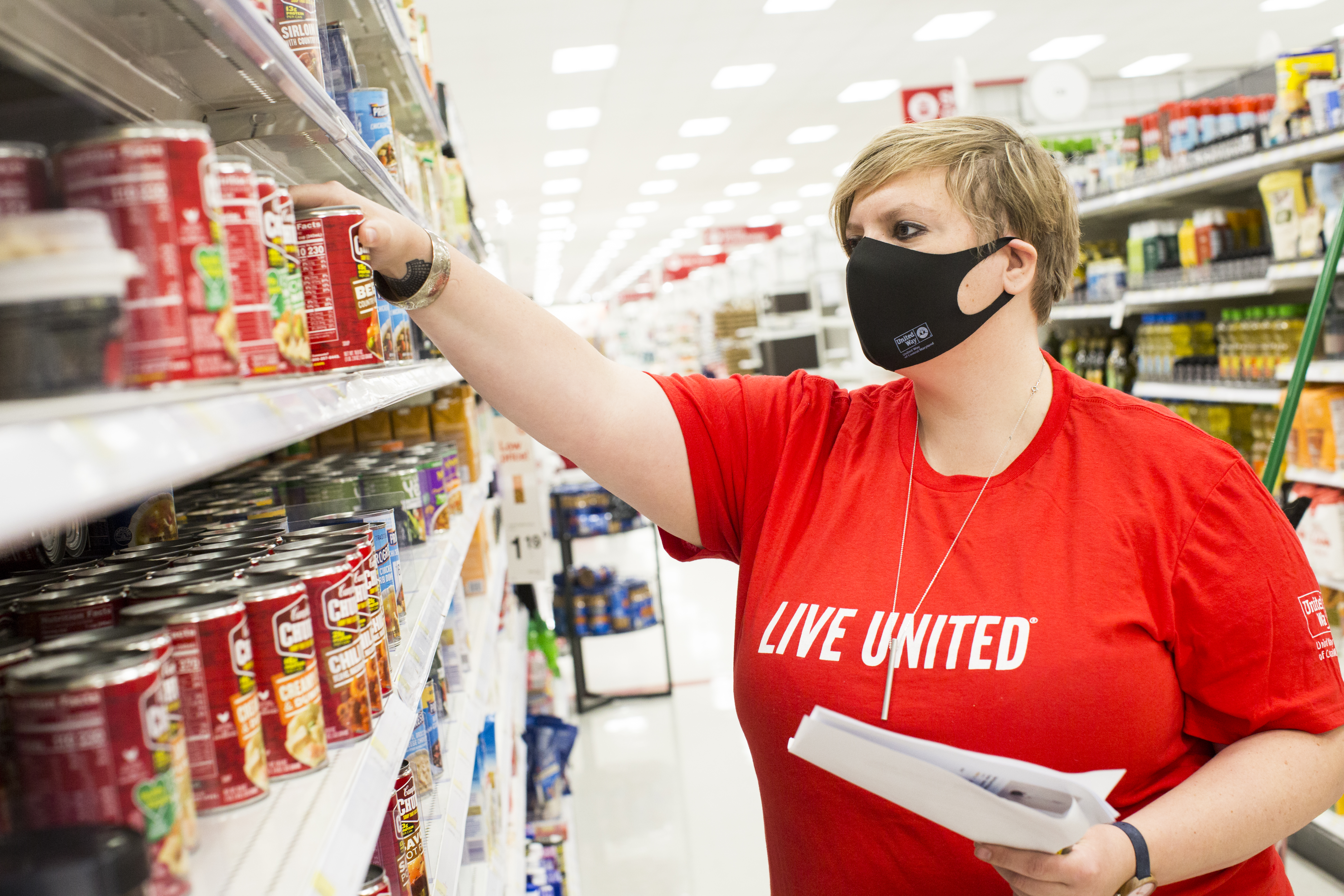 UWCM volunteer in  Live United shirt purchasing canned food at store