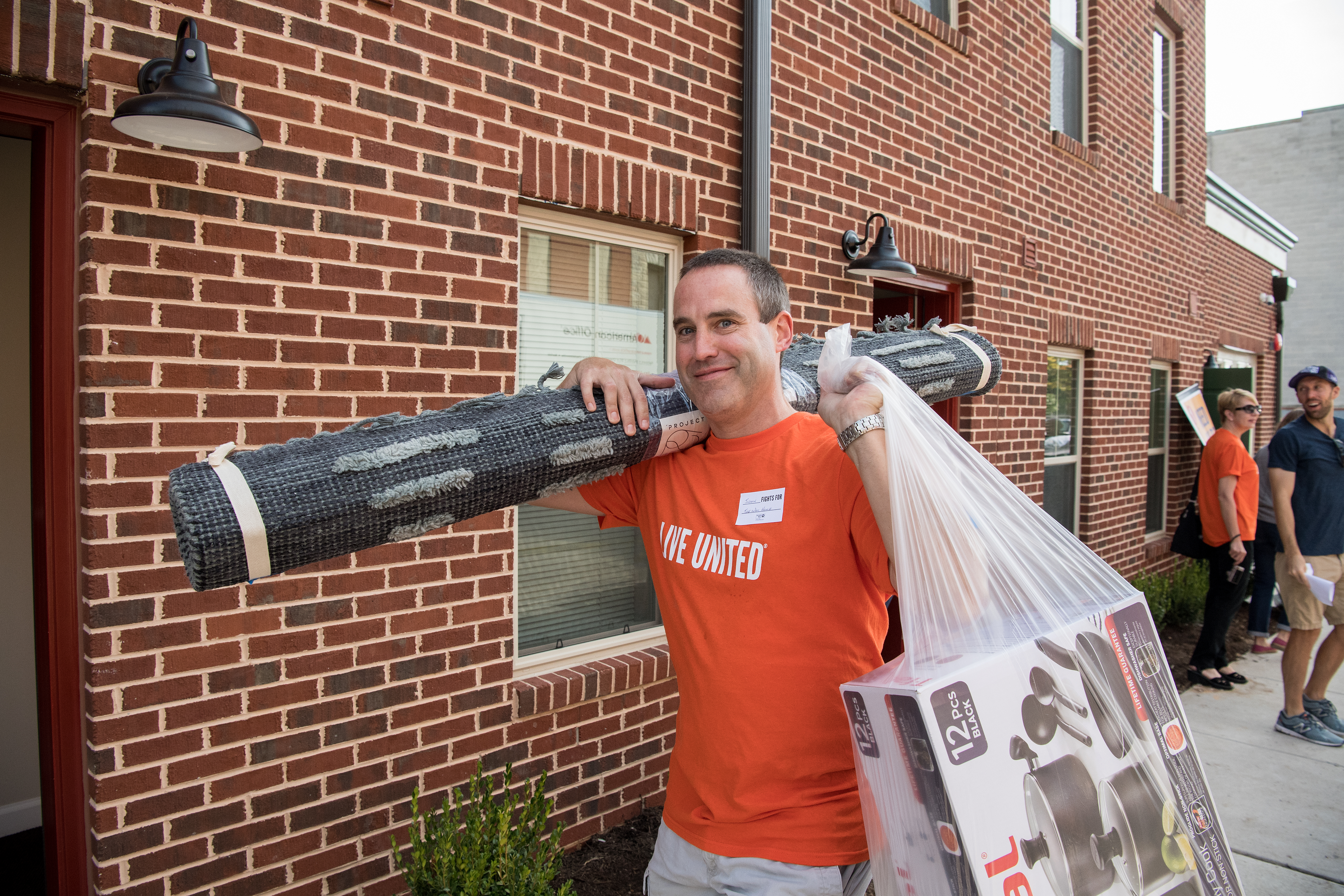 A Leaders United member in his Live United shirt carries household items to be installed in one of the Way Home project homes.