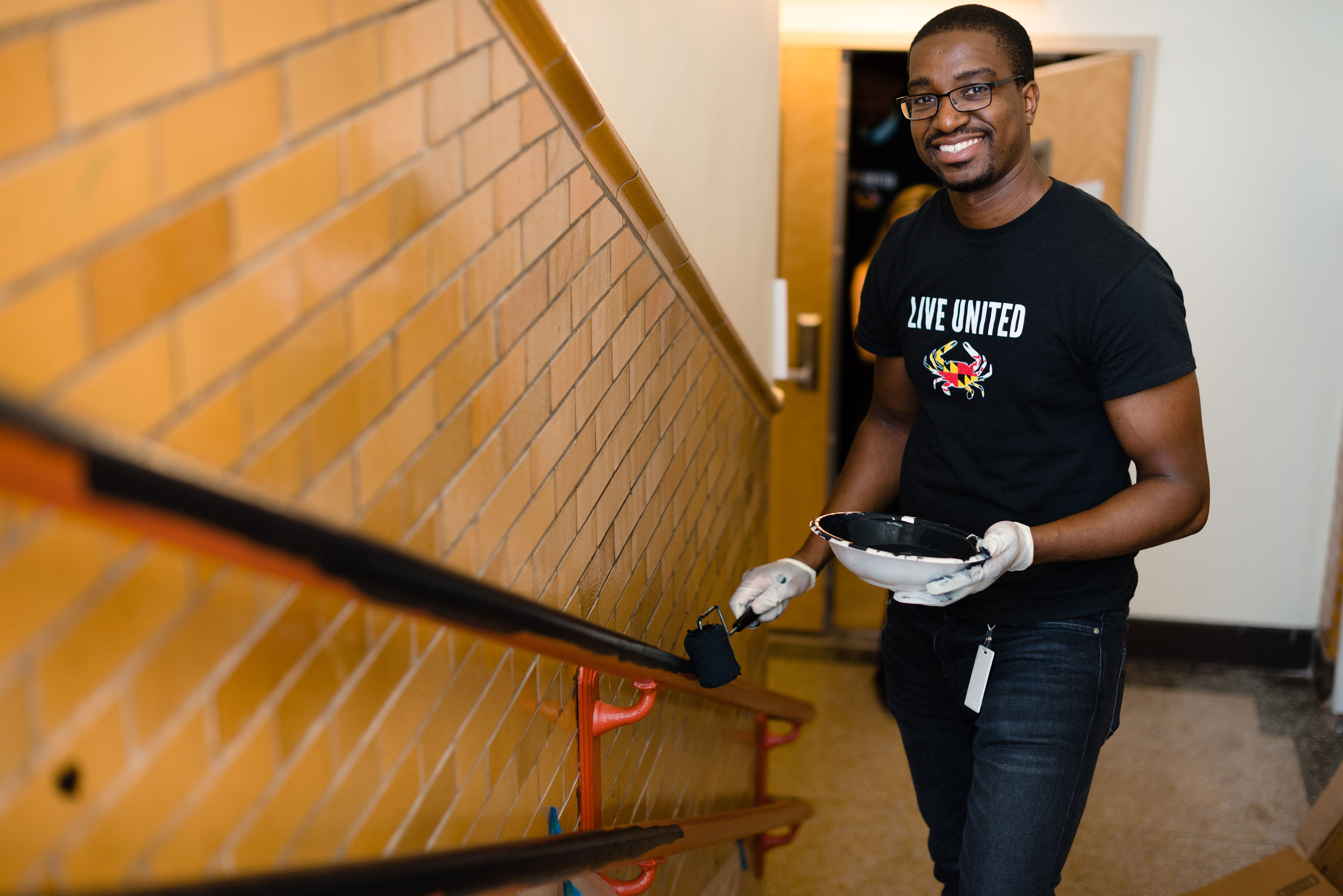 An Emerging Leaders United member volunteering to paints a railing at a clean up project