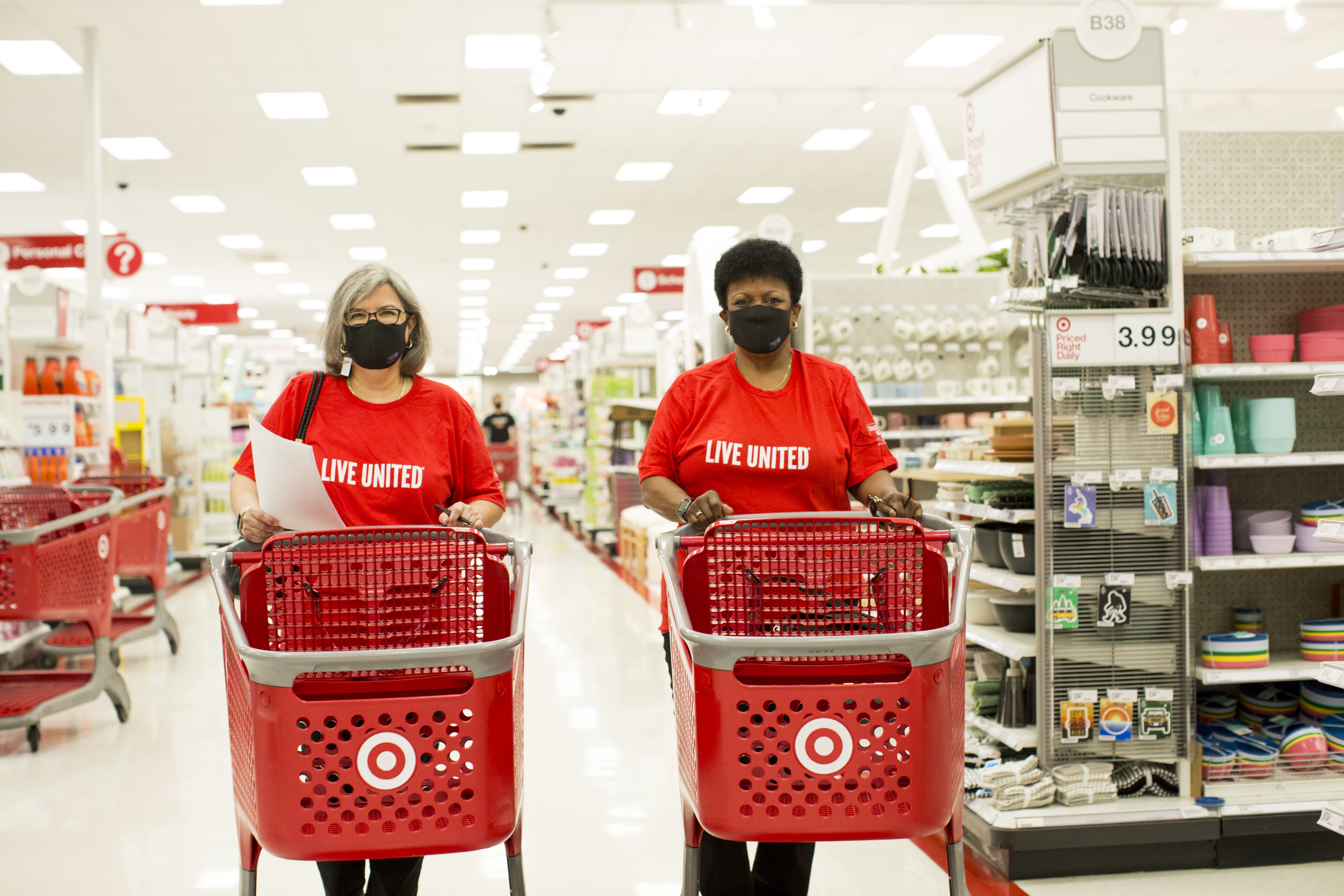 Two Leaders United member in Live United shirt shop at Target for items needed for The Way Home project