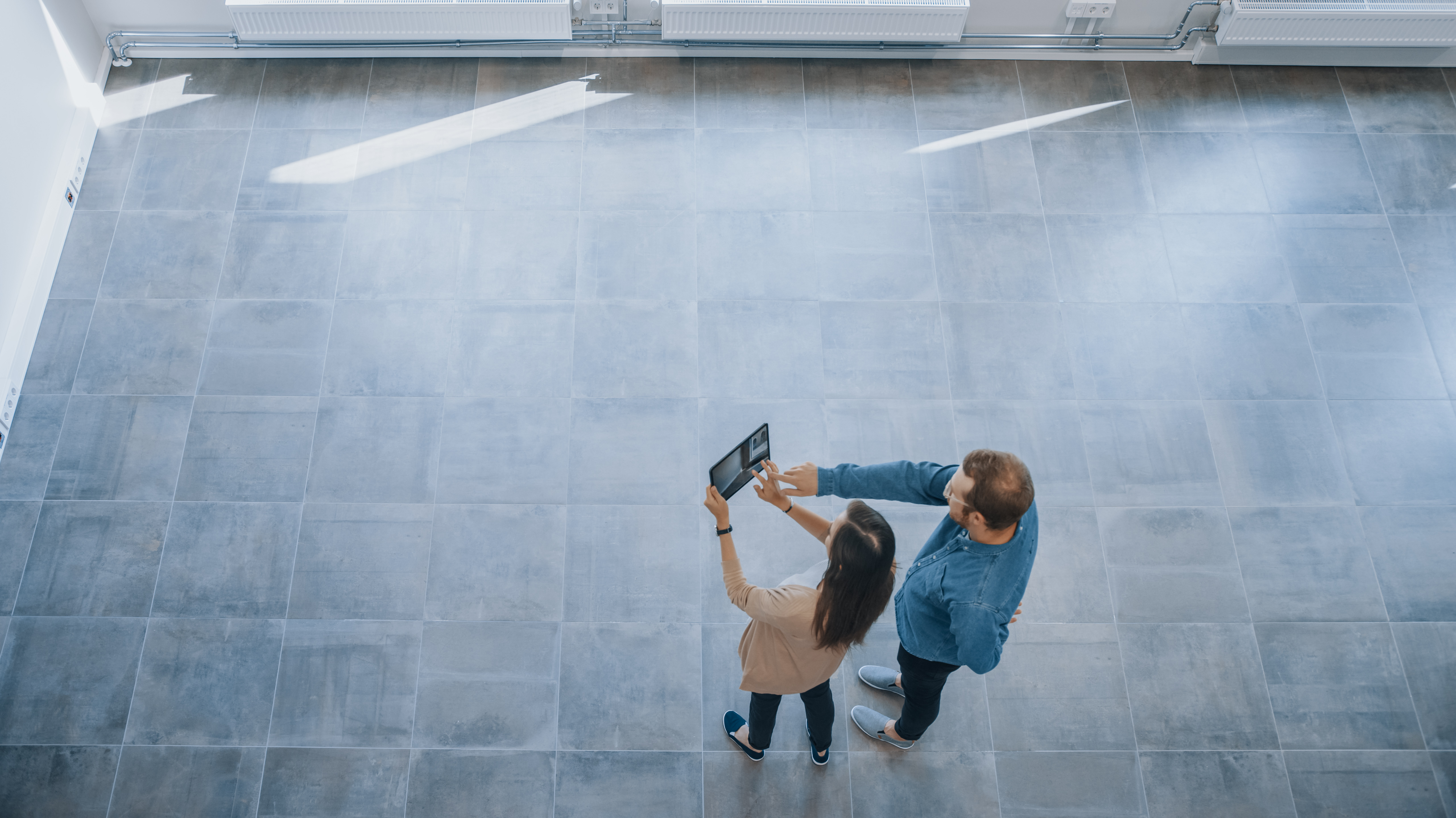 Young Hipster Man and Female Stand in an Empty White Office and Map it with an Augmented Reality Software on a Tablet. Sunlight Shines Through Big Windows.